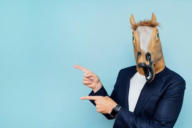 Homem com máscara de cavalo apontando para o lado. espaço da cópia.
