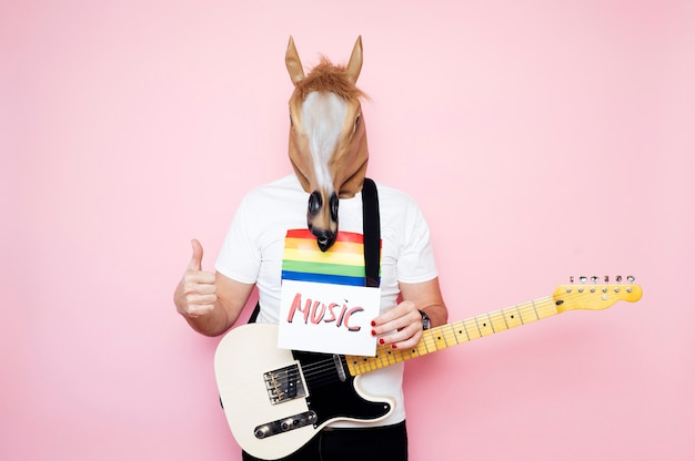 Homem com máscara de cavalo com o polegar para cima segurando uma placa que diz