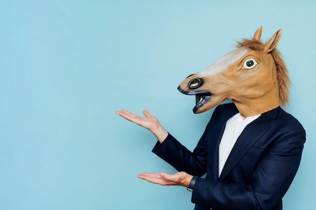 Homem com máscara de cavalo mostrando a palma da mão aberta com espaço de cópia para produto ou texto