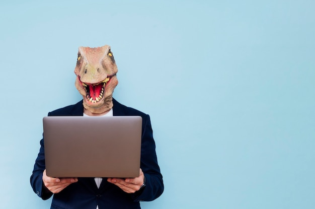 Homem com máscara de dinossauro, consultoria em laptop. fundo azul