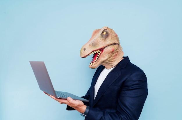Homem com máscara de dinossauro, fundo azul Foto Premium