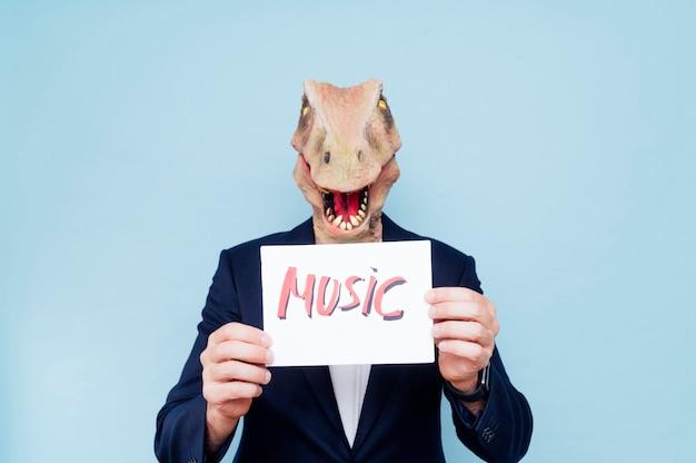 Homem com máscara de dinossauro segurando uma placa que diz música
