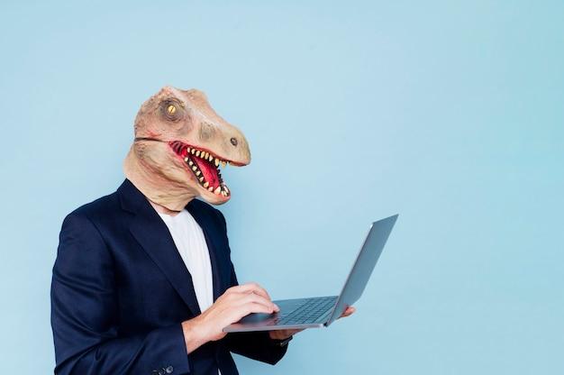 Homem com máscara de dinossauro usando laptop