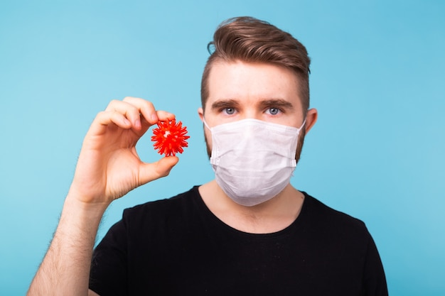 Homem com máscara de gripe segura modelo de coronavírus