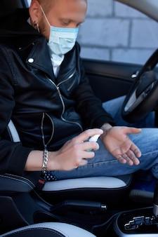 Homem com máscara de proteção sentado no carro, pulverizando as mãos spray desinfetante antibacteriano para prevenção de coronavírus