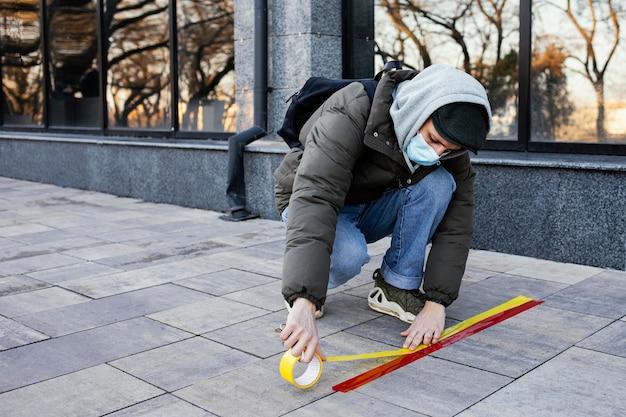 Homem com máscara definindo faixa de distância social