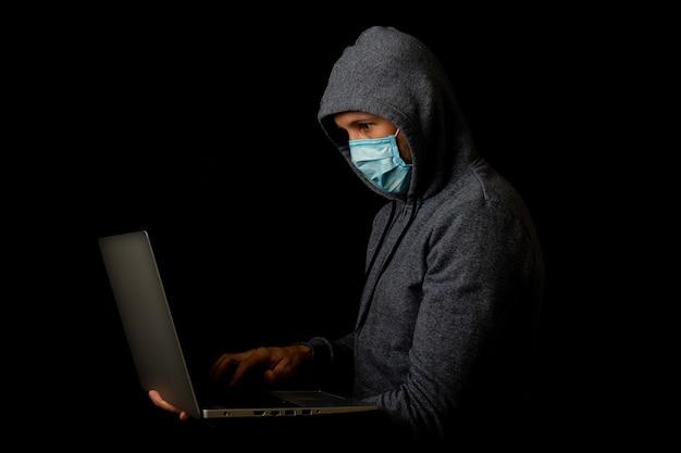 Homem com máscara e capuz segura um laptop nas mãos em um escuro
