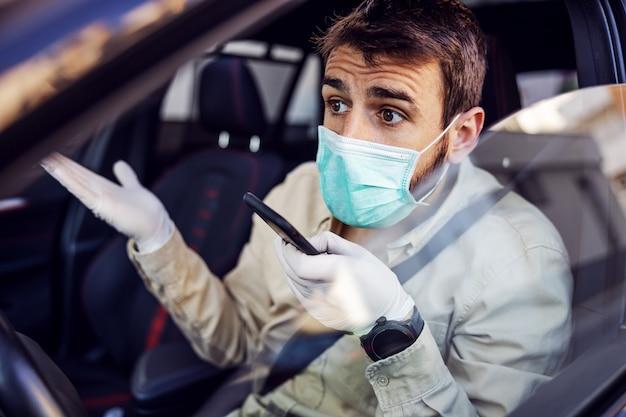 Homem com máscara e luvas dirigindo um carro, falando no smartphone do telefone móvel. prevenção de infecções e controle de epidemia. pandemia mundial. fique seguro.