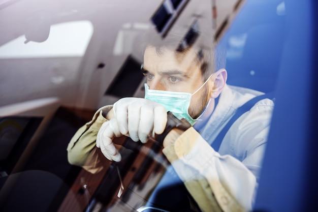 Homem com máscara e luvas, dirigindo um carro. prevenção de infecções e controle de epidemia. pandemia mundial. fique seguro.