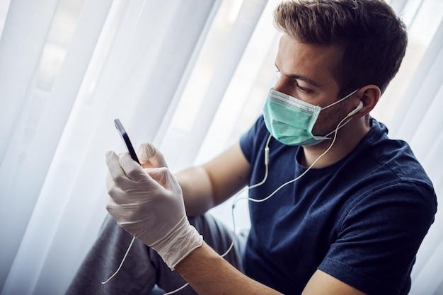 Homem com máscara e luvas, ouvindo música e digitando no smartphone. ficar em casa. pandemia mundial, coronavírus.