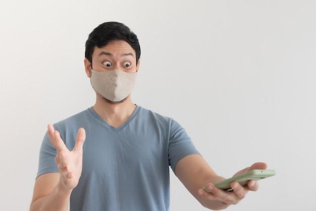 Homem com máscara está feliz com a promoção no aplicativo para smartphone.