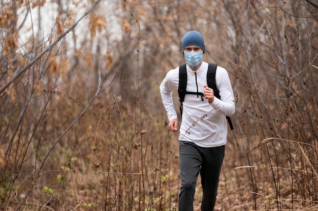 Homem com máscara facial correndo na floresta