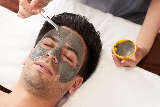 Homem com máscara facial de argila