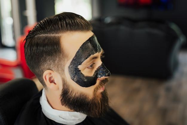 Homem com máscara facial de carvão preto, conceito de cuidados com a pele, limpeza de poros de acne.