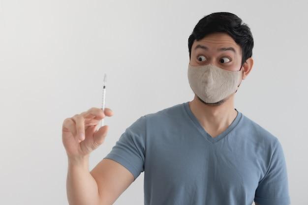 Homem com máscara facial está injetando uma vacina. conceito de proteção contra vírus.