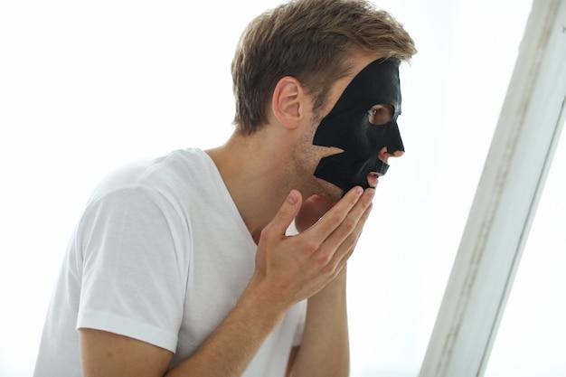 Homem com máscara facial preta, carvão purificador de pele. conceito de beleza