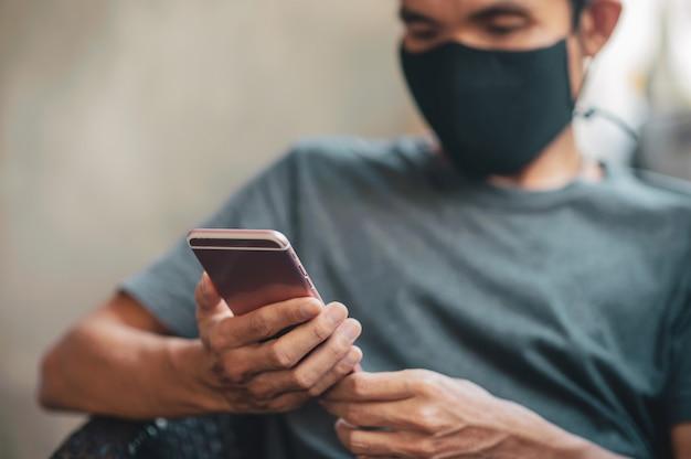 Homem com máscara facial usando smartphone