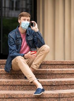 Homem com máscara falando ao telefone