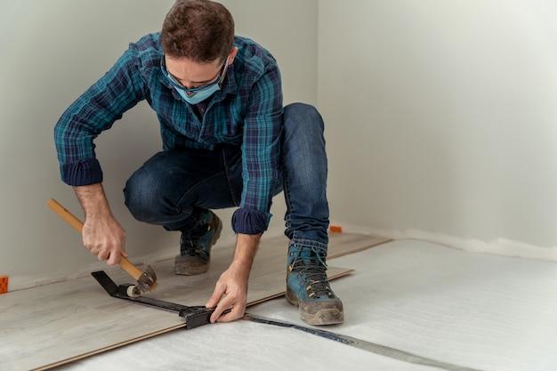 Homem com máscara instalando piso de madeira com ferramentas para sua instalação