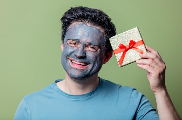 Homem com máscara limpa e caixa de presente
