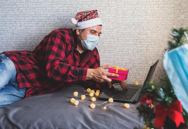 Homem com máscara médica compartilhando presentes de caixa por meio de videochamadas