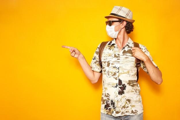 Homem com máscara médica cruzou as mãos em forma de coração em sinal de amor sobre fundo amarelo