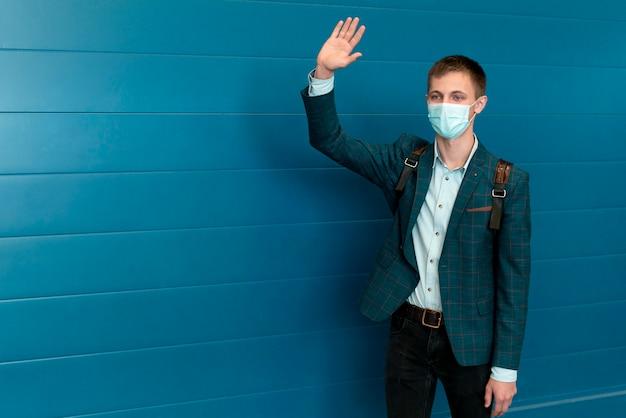 Homem com máscara médica e mochila acenando