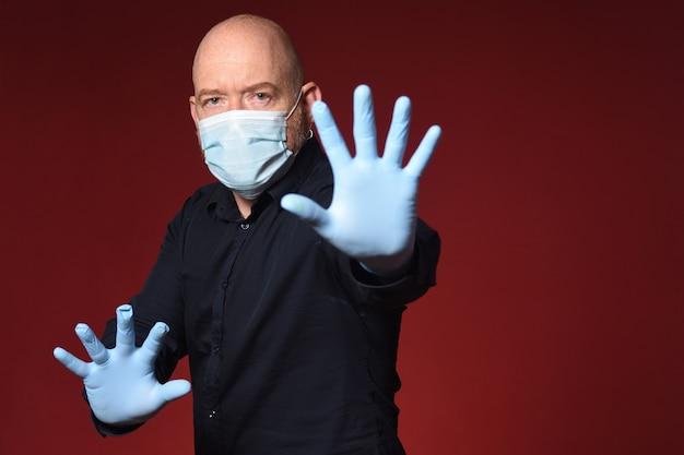 Homem com máscara médica e placa de pare no bacground vermelho