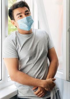 Homem com máscara médica em casa durante a pandemia sentado ao lado da janela