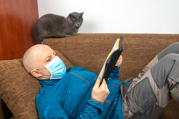 Homem com máscara médica em casa em quarentena por causa de uma epidemia de coronavírus lê a bíblia sentado em um sofá ao lado de um gato cinza
