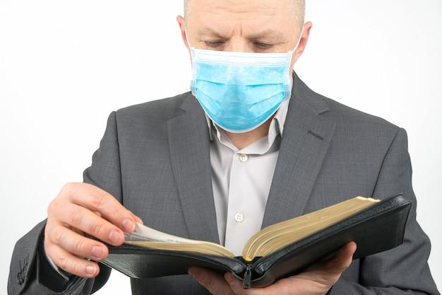Homem com máscara médica está estudando a bíblia. religião e cristianismo.