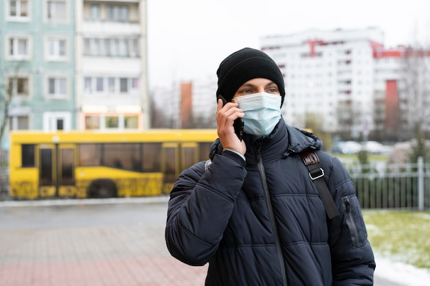 Homem com máscara médica falando ao telefone na cidade
