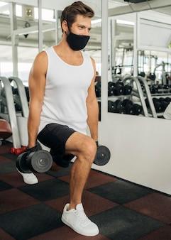 Homem com máscara médica malhando na academia