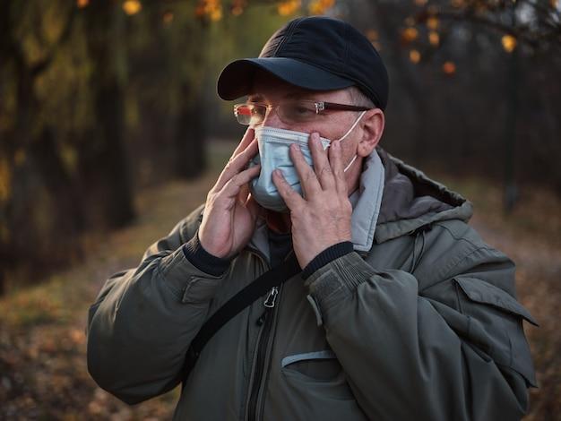 Homem com máscara médica no parque outono