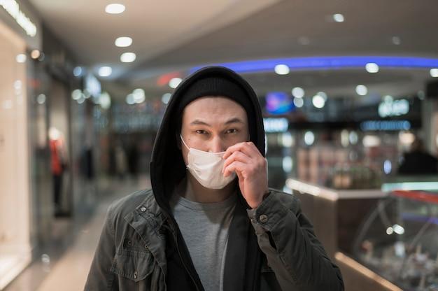 Homem com máscara médica no shopping