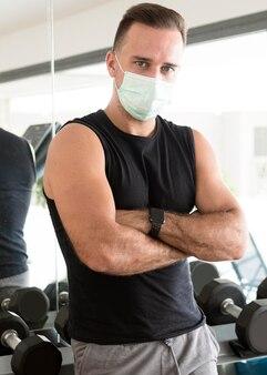 Homem com máscara médica posando no ginásio