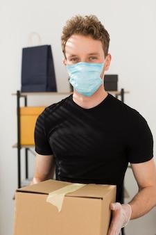 Homem com máscara médica segurando a caixa