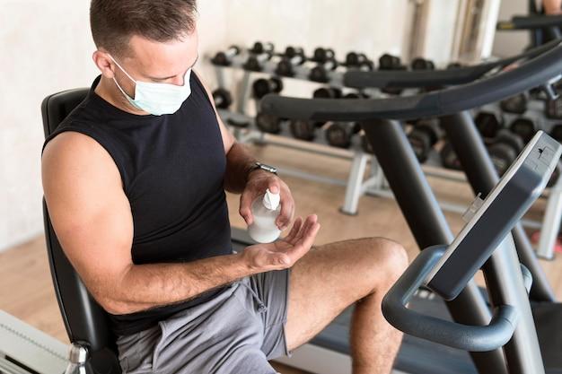 Homem com máscara médica usando desinfetante para as mãos na academia