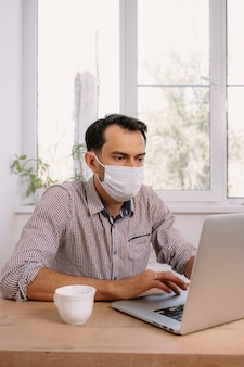 Homem com máscara médica usando laptop em casa