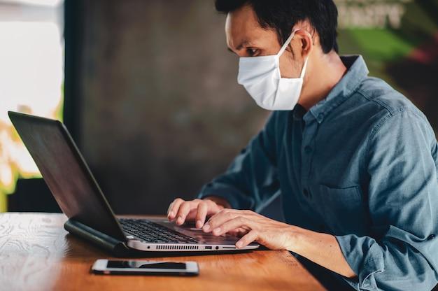Homem com máscara médica usando um laptop