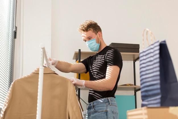 Homem com máscara olhando roupas