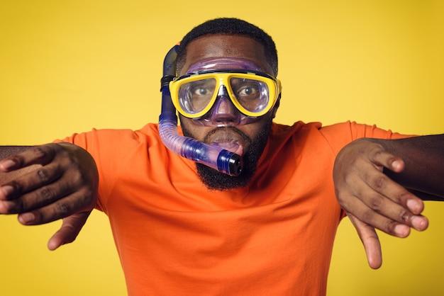 Homem com máscara pronta para nadar debaixo d'água. parede amarela