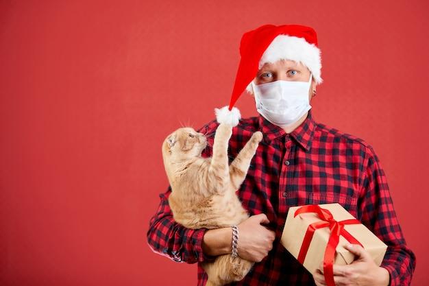 Homem com máscara protetora e chapéu de papai noel com presente de natal diy e um gato