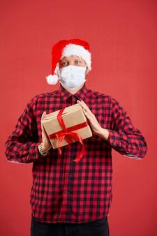 Homem com máscara protetora e chapéu de papai noel com presente de natal diy