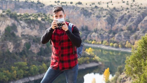 Homem com máscara protetora na montanha tirando fotos