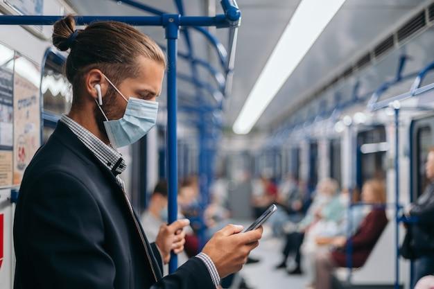 Homem com máscara protetora parado em um vagão do metrô