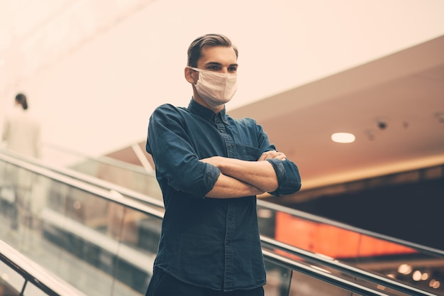 Homem com máscara protetora parado na escada da escada rolante do metrô