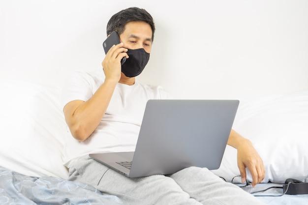 Homem com máscara protetora que fala no telefone celular com o laptop nas regaços que trabalham do conceito home.
