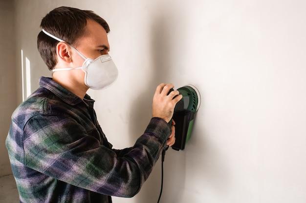 Homem com máscara protetora trabalhando com lixadeira elétrica para alisar a superfície da parede de gesso, conceito de renovação de sala
