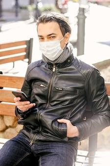 Homem com máscara protetora usando telefone celular